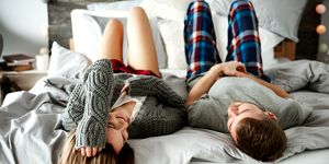 Couple Lying Down On Bed At Home