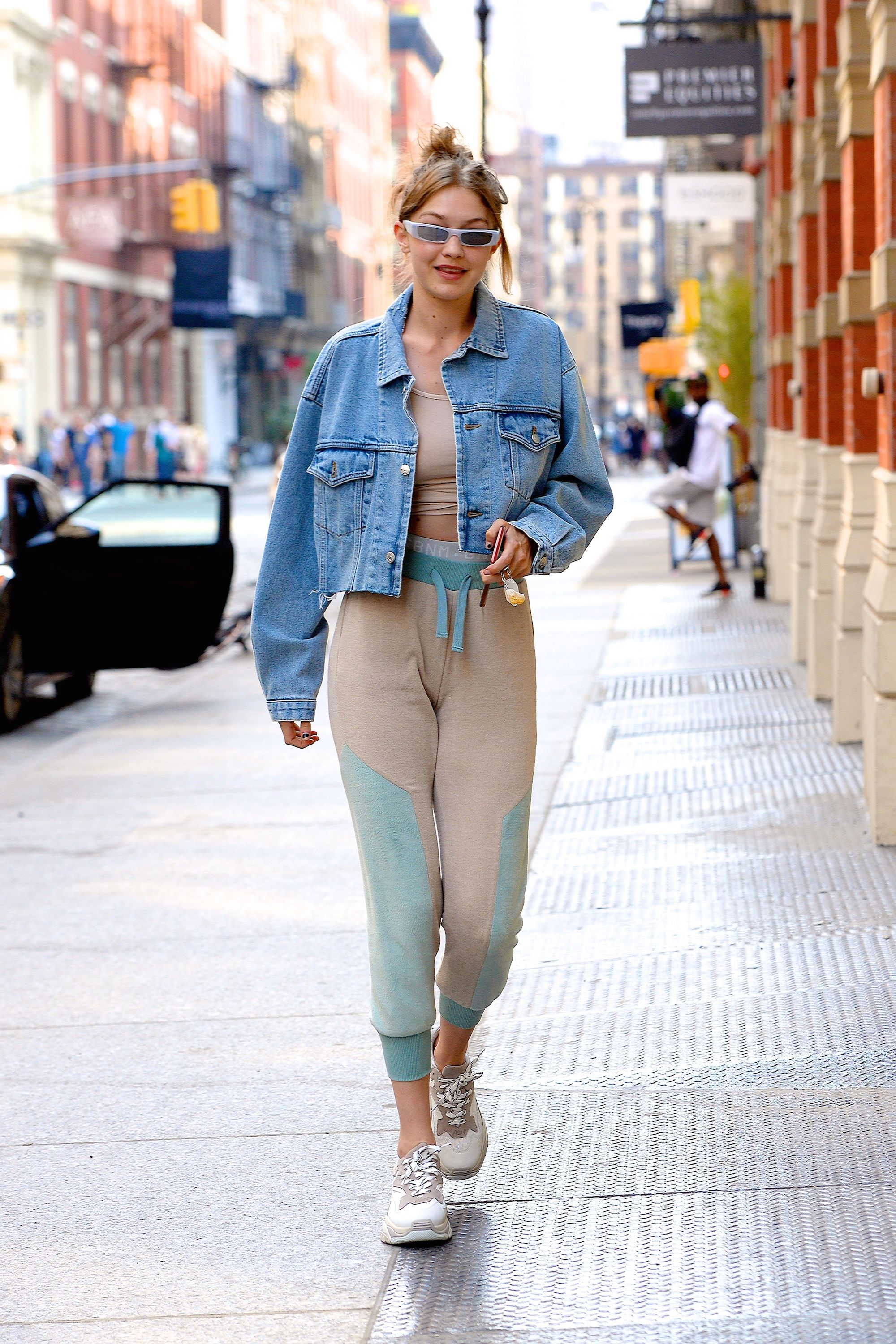June 18, 2018 Hadid left her apartment in a cool pair of two-toned sweatpants by Sebnemgunay. She styled the look with a cropped denim jacket from the Miss Sixty x Elizabeth Sulcer collection and wore her fave Ash sneakers and Alexandre Vauthier x Alain Mikli sunglasses.