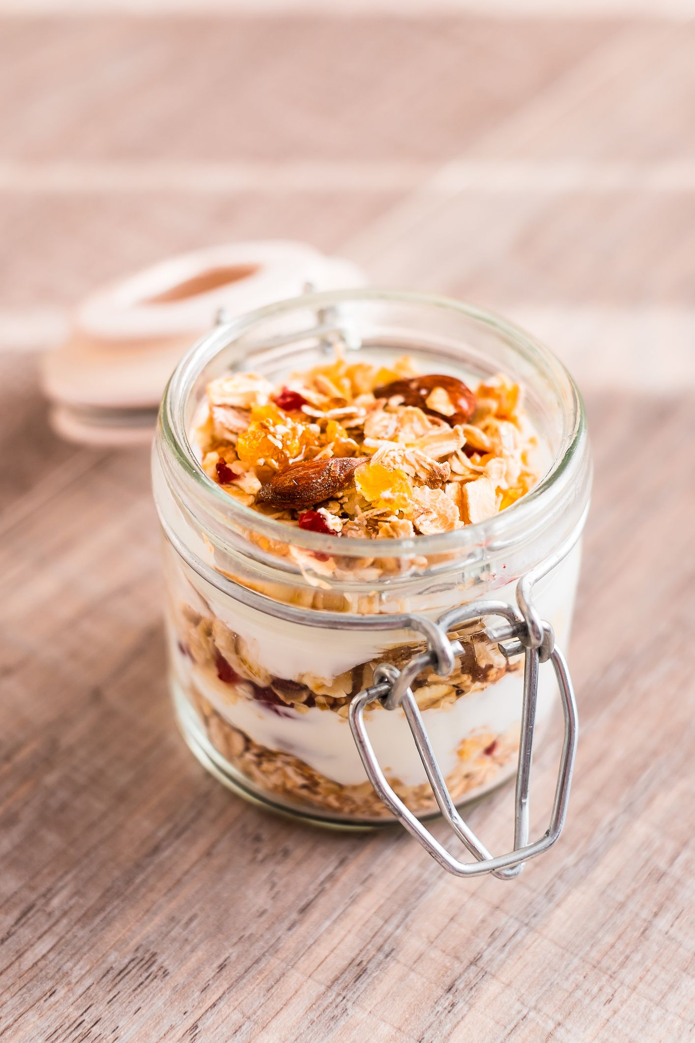 Traditional breakfast from Switzerland. Jar of homemade muesli bircher with plain yogurt, toasted oat flakes, almonds, peanuts, dried fruits and honey on a wooden table, selective focus. Organic food.