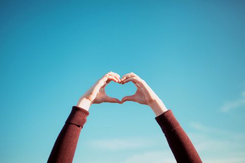 womans hand gesturing a heart shape over clear blue sky and warm sunlight