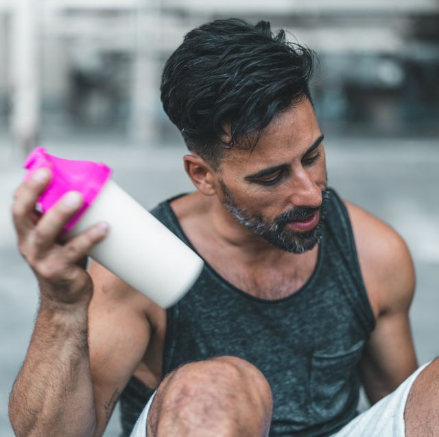 a man is sitting down to mix a protein shake after en exercise inside an abandoned warehouse
