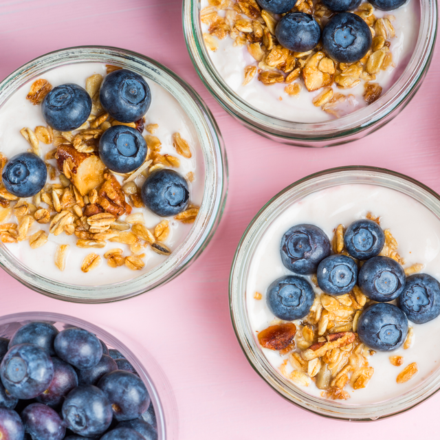 jars filled with yogurt, blueberries, and granola on pink background