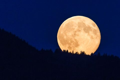 Supermoon glowing against blue sky