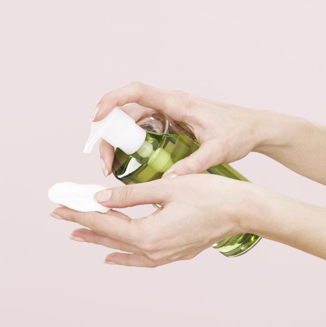 female hands, green liquid, make up remover, clear plastic bottle, dispenser, white cotton pad, pink background