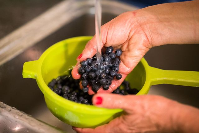 illustration   30 june 2018, oldenburg, germany a woman washing blueberries photo mohssen assanimoghaddamdpa photo by mohssen assanimoghaddampicture alliance via getty images