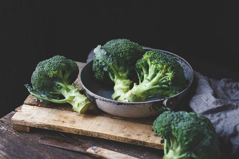 Close-Up Of Broccolis On Wooden Table Against Black Background