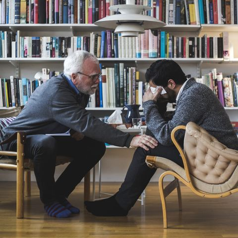 Senior therapist counseling young patient while sitting by bookshelf during therapy session