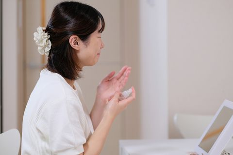 woman using skin lotion spray for face care