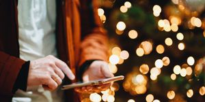 Midsection Of Man Using Smart Phone Against Illuminated Christmas Tree