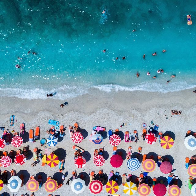 Aerial View Of Colorful Umbrellas On Shore At Beach