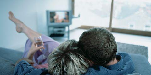 Pareja viendo una película en el sofá de casa.