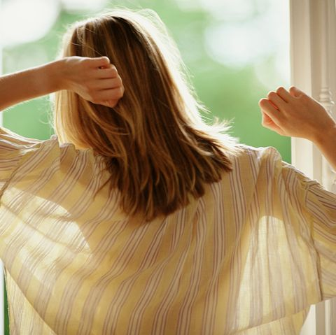 Woman next to open window, stretching, rear view
