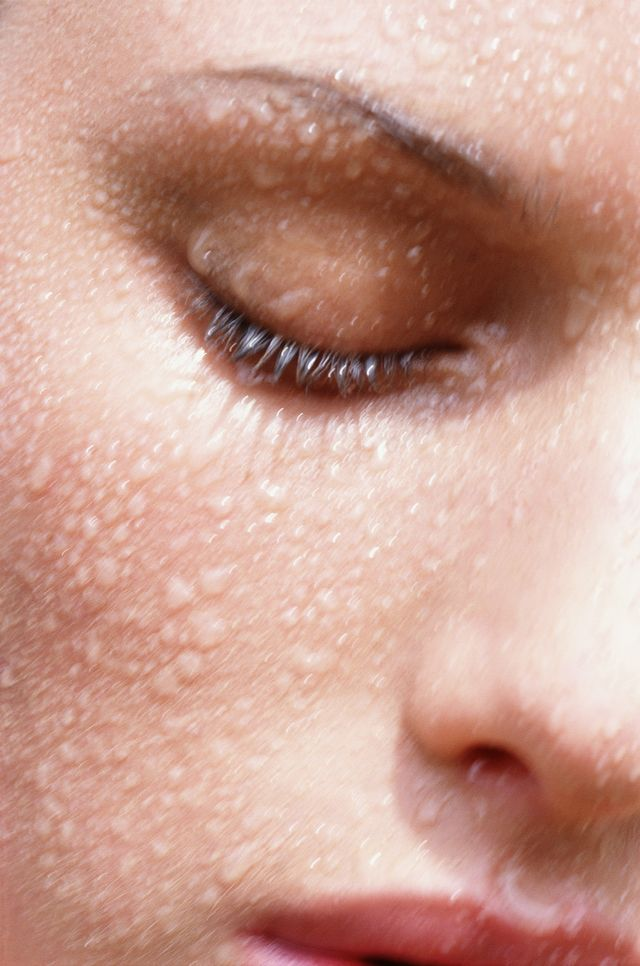 woman with eyes closed with water on face, close up
