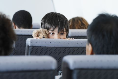 Young boy looking over a seat in an airplane