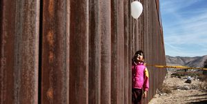 A little girl holds a white ballon at the border wall between Mexico and the United States
