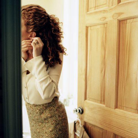 Woman putting on earrings in bathroom