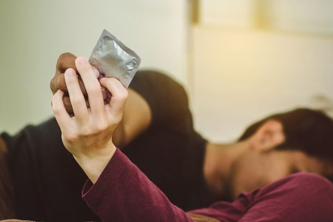 Close-Up Up Couple Holding Condom Lying On Bed At Home