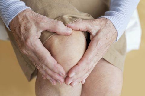 Senior woman holding sore arthritis knee