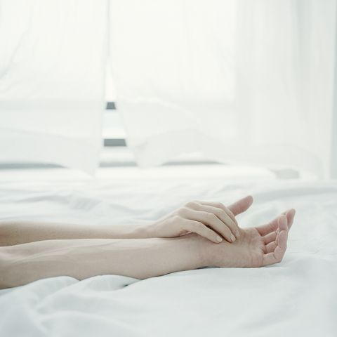 Young couple's arms on bed, hands touching