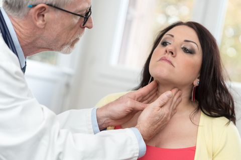 Doctor performing thyroid exam on woman