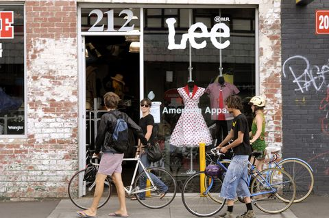 People walking with bicycles past clothing store on Brunswick Street, Fitzroy.