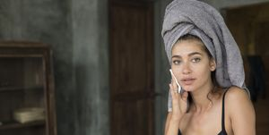 Woman with a towel on hear head removing make-up