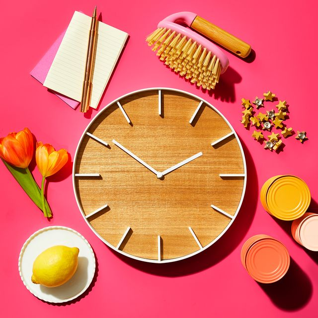 wooden clock with flowers cans notepad and lemon on a plate