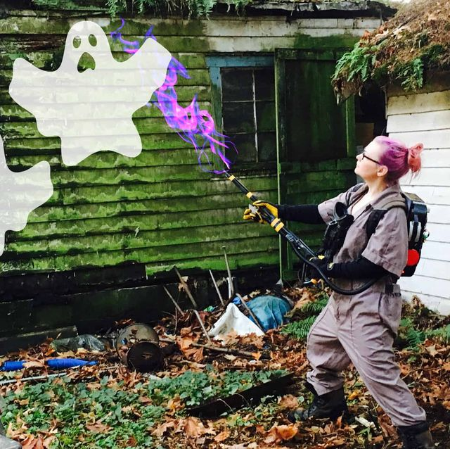 woman in ghostbusters costume fighting white ghosts