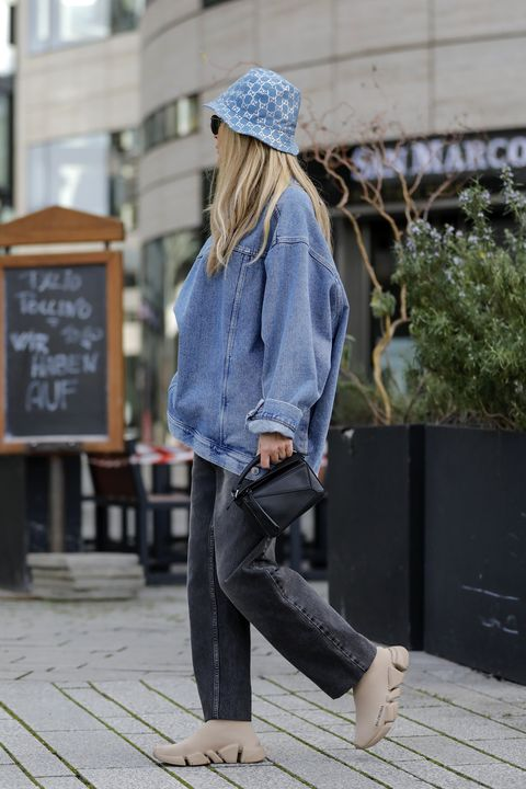dusseldorf, germany   february 12 influencer gitta banko wearing a light blue gg lame bucket hat by gucci, grey denim jeans pants by balenciaga, a light blue denim jeans blouse by balenciaga, a black mini bag by loewe, beige sneaker by balenciaga and sunglasses by ray ban all by breuninger during a street style shooting on february 12, 2021 in dusseldorf, germany photo by streetstyleshootersgetty images