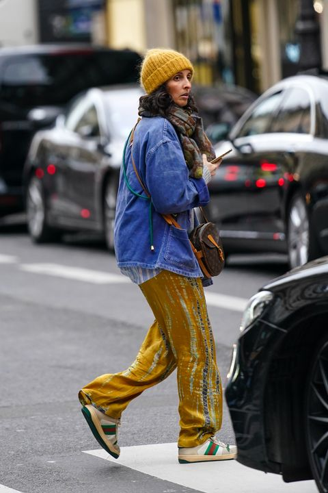 paris, france   february 28 a guest wears a yellow knit beanie hat, a grey and brown print scarf, a louis vuitton monogram crossbody bag, yellow and grey print wide legs full length pants, light grey sneakers with red and green stripes, outside nina ricci, during paris fashion week   womenswear fallwinter 20202021, on february 28, 2020 in paris, france photo by edward berthelotgetty images