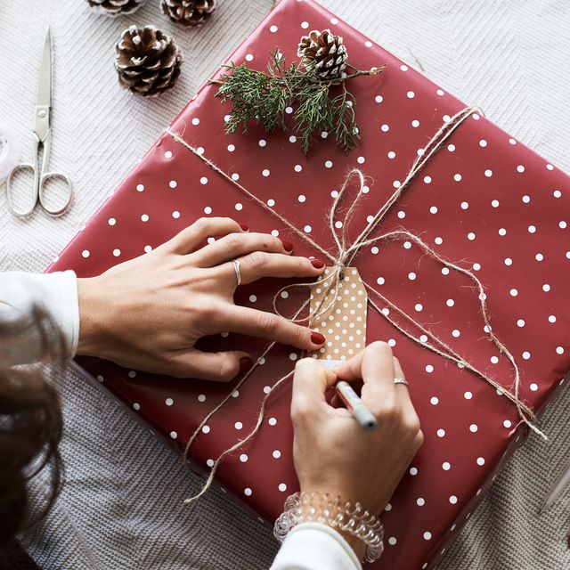 woman writing on gift tag on top of wrapped gift