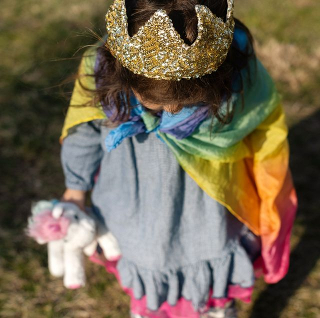 three year old girl with crown and rainbow cape on carrying unicorn toy