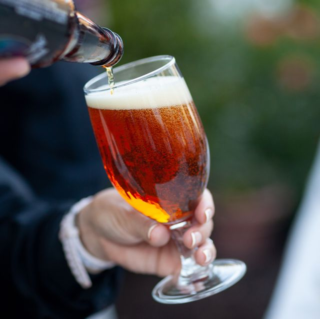 person holding glass while beer is poured