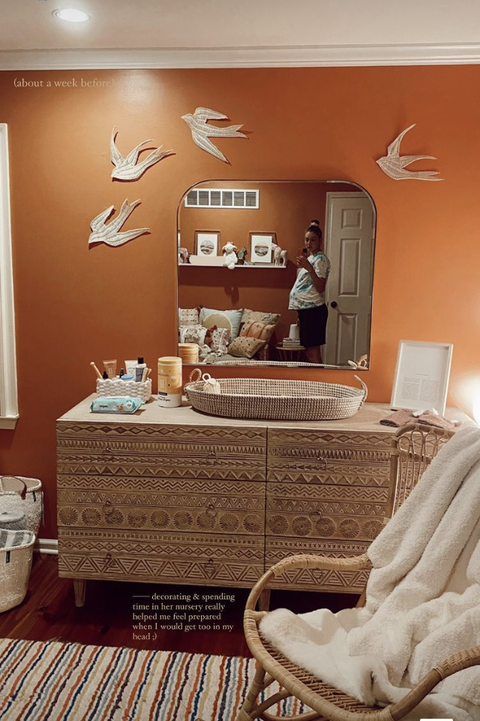 burnt orange wall with aztec dresser, basket, mirror, doves on wall