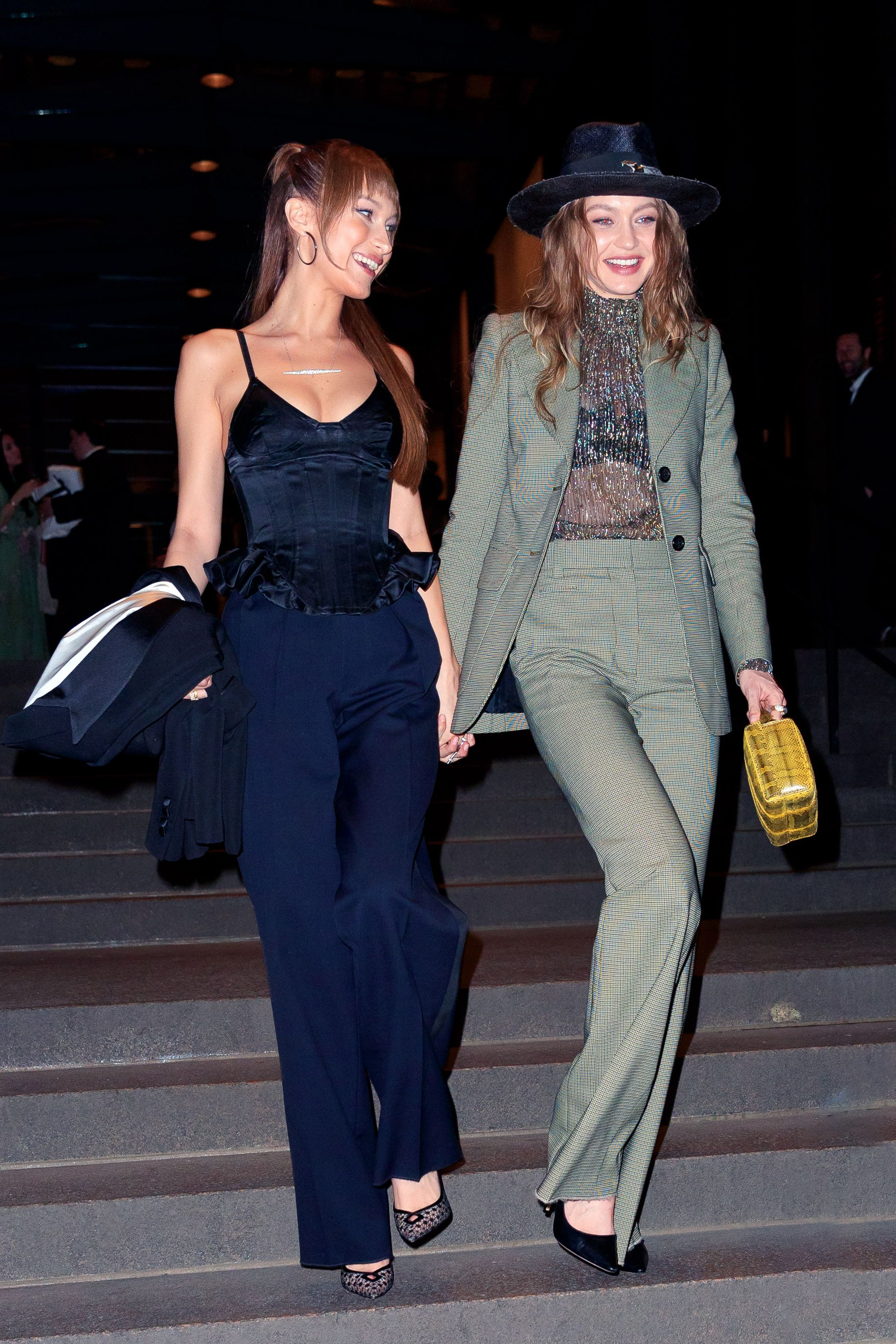 April 7, 2019 For Marc Jacobs' wedding in NYC, the Hadid sisters went with smart suited ensembles. While Bella opted for a peplum top and navy trousers, Gigi wore a gray two-piece suit with a sheer high-neck top that showed off her bra.