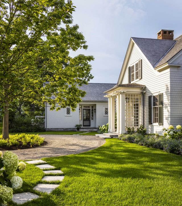 a white cottage style home with a green lawn