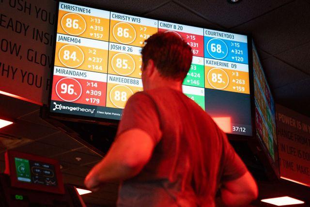 un hombre entrena en un gimnasio con varias pantallas para seguir su rendimiento