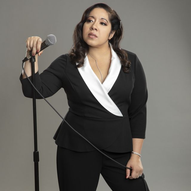 gina brillon wearing a black and white suit holding a microphone
