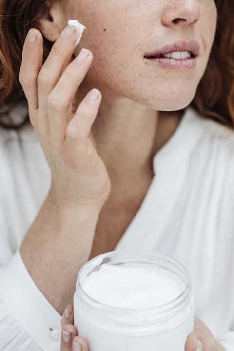 Ginger haired woman applying facial cream