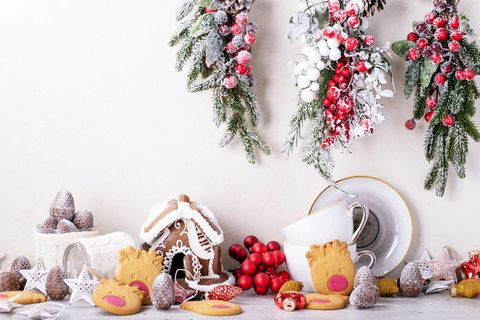 Gingerbread House And Christmas Decoration Against White Wall