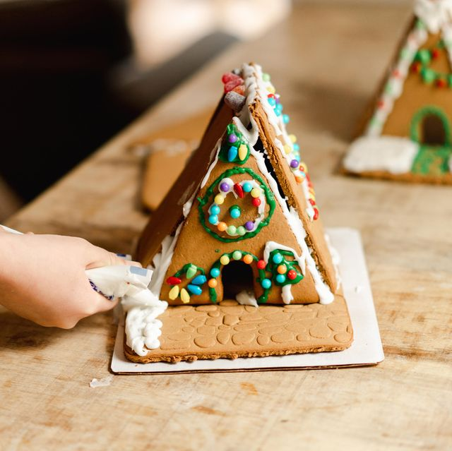 kid putting icing on gingerbread house