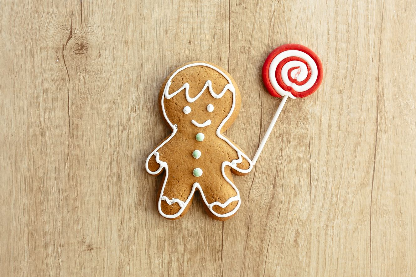 Gingerbread man holding lollipop on a wooden background