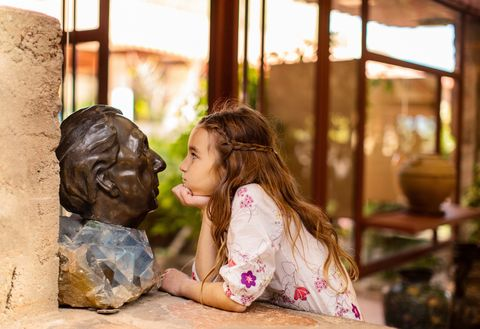 young girl staring closely at Frank Lloyd Wright bust