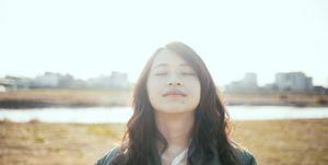 Girl closing her eyes at the river bank