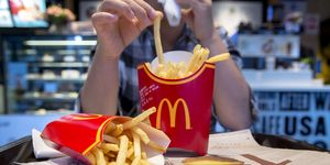 A girl eats fried chips in a McDonald's restaurant...