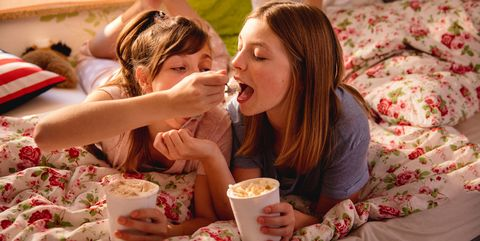 Girl feeding her friend ice cream from a tub