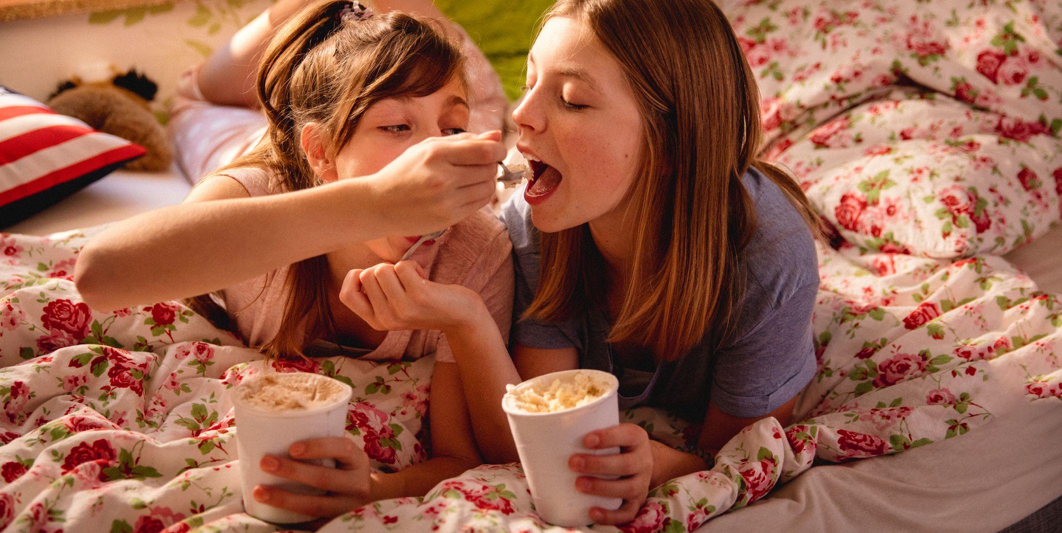 Girl feeding her friend ice cream from a tub