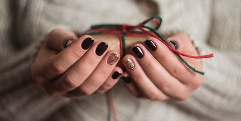 girl holding a gift box. Manicure gel nail