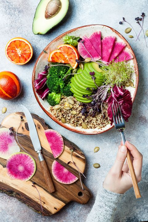 girl holding fork and eating vegan, detox buddha bowl with quinoa, micro greens, avocado, blood orange, broccoli, watermelon radish, alfalfa seed sprouts