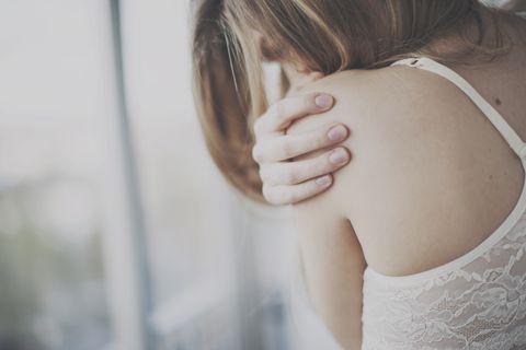 girl hugging self